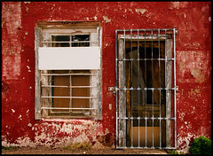 Bisbee Red Wall (Junkstock) Tags: door old windows red arizona color building texture abandoned window wall architecture buildings photography photo junk paint doors exterior photos decay rustic textures photographs photograph weathered aged peelingpaint bisbee distressed corrosion patina ruralexploration oldandbeautiful agedwindow
