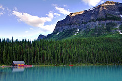 In the Mountain's Shadow (Jim Boud) Tags: travel blue red sky mountain lake snow canada reflection building tree green nature water pinetree clouds forest canon lens landscape outdoors eos boat nationalpark cabin colorful hiking rental wideangle canadian canoe glacier shore alberta northamerica banff dslr lakelouise digitalrebel photoart 1022mm digitalslr pinetrees province firtree waterscape artisticphotography superwideangle canadianrockies efs1022mm photomatix 550d jimboud t2i exposurefusion jamesboud eos550d kissx4 blendlayers