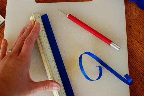 cutting strip of blue paper using a ruler and exacto knife