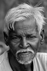 Toddy Seller- Orissa (Shubh M Singh) Tags: old light portrait india white man texture monochrome smile rural dark hair beard nose eyes nikon dof skin labor personality booze farmer d200 nikkor orissa unshaven toddy cuttack