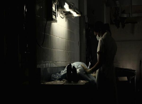 a creepy scene where a surgeon figure standing over a prone body. It looks like it's in a dark basement.