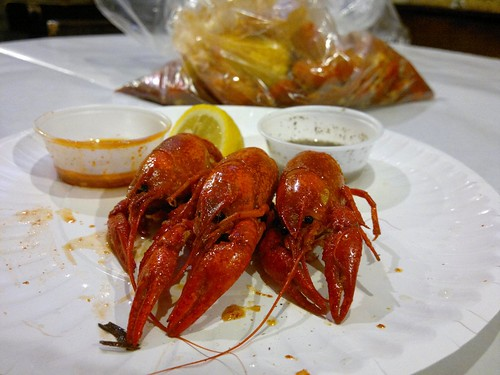 Three boiled hot crawfish with the remainder of the pound in the plastic bag behind