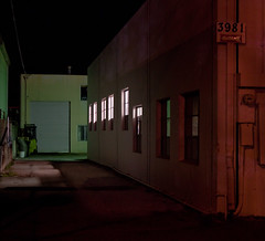 What Happens Inside? (waxyleaves) Tags: windows light red building green night alley shadows garage creepy cast unknown mysterious dim verite