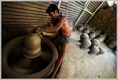 The Maestro of Clay [..Chuadanga, Bangladesh..] (Catch the dream) Tags: man motion wheel artist pattern mud top creative potter social pots soil hut motionblur clay pottery rotation worker economy bangladesh claypots microfinance skill skillful earthen chuadanga earthenpots topangle gettyimagesbangladeshq2