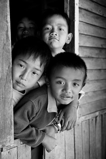 Boys in Burma peek out a window. The future they'll see is in transitio