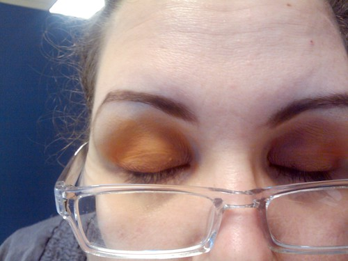 Both closed eyes, with eyeshadow in warm, matte shades of yellow and orange
