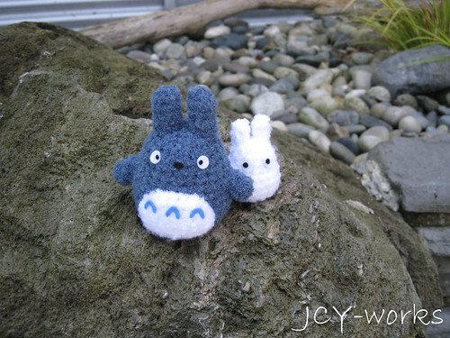 chibi and chu Totoro climbing past a rocky mountain.