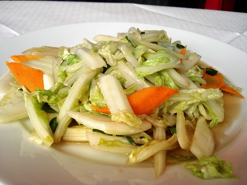 A plate of Chinese leaf/Chinese cabbage cut into bite-size pieces and piled up with a few bits of similarly-cut carrots to provide colour.  A light vinegar sauce coats the vegetables and pools shallowly on the plate.