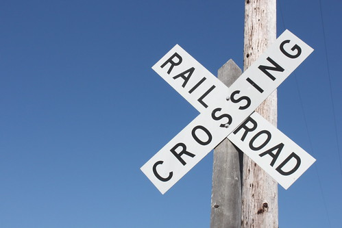 A railroa crossing sign, shot against a bright blue sky.