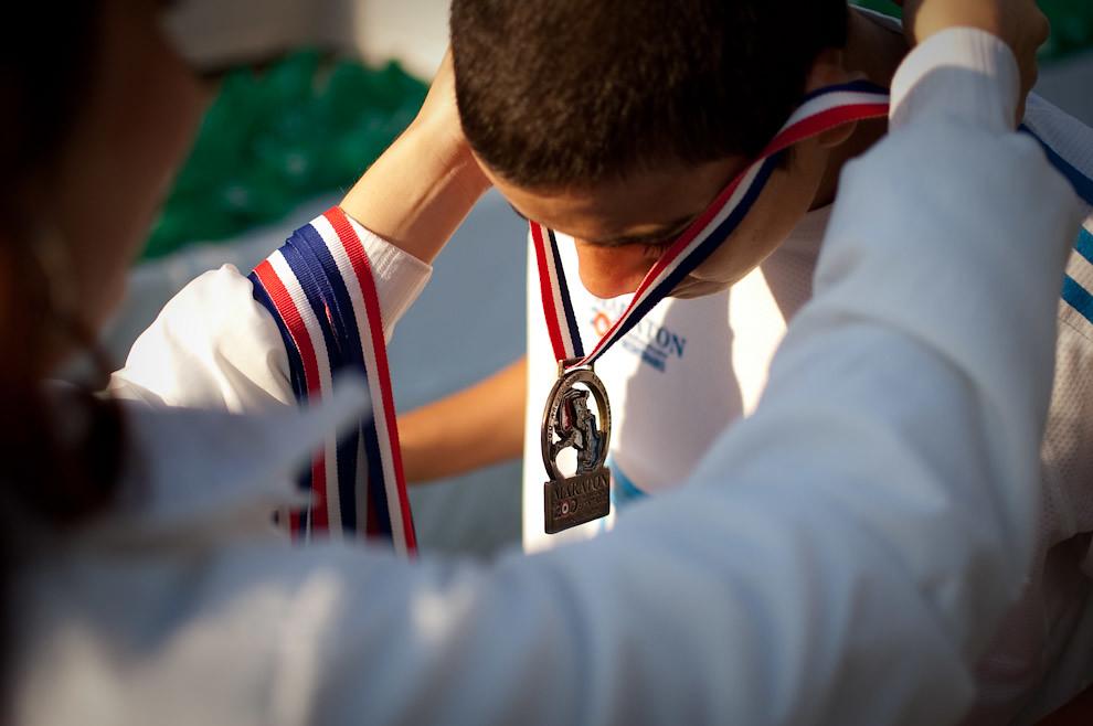 Un atleta recibe su galardón de participación por parte de laspromotoras del Banco Vision.  (Elton Núñez - Asunción, Paraguay)