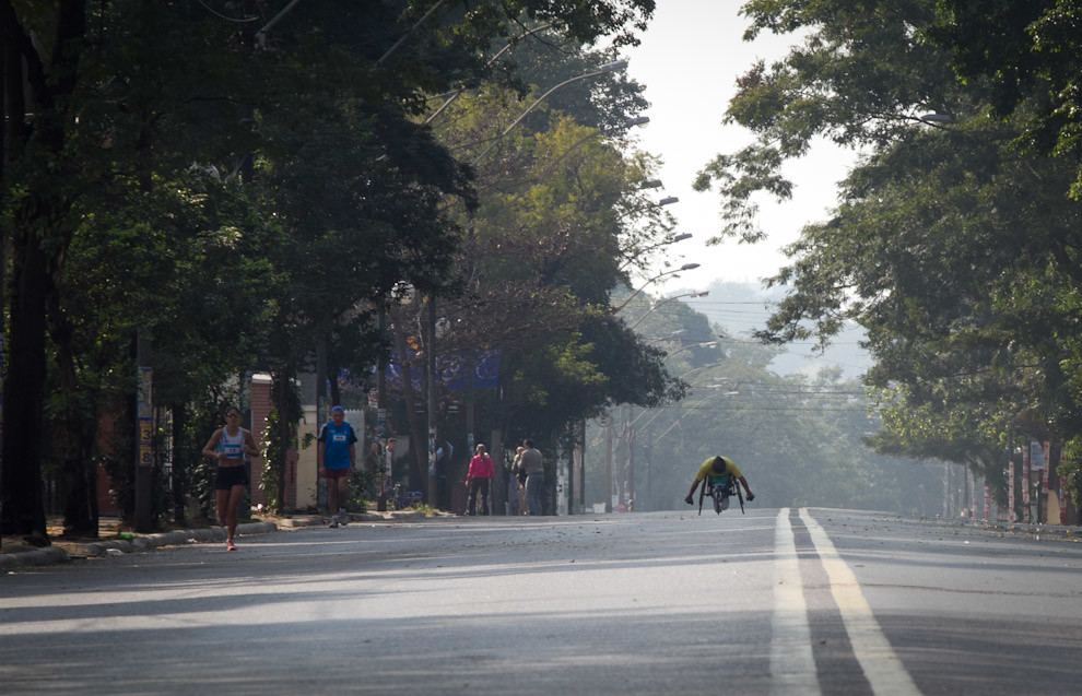 Carlos Roberto Oliveira avanza a toda velocidad sobre Mcal Lopez a la altura de Mburivicha Roga manteniendo su primer puesto en la categoria 42k en silla de ruedas. (Tetsu Espósito - Asunción, Paraguay)