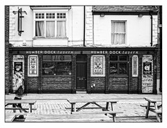 Humber Dock Tavern (A.I.D.A.N.) Tags: humberdocktavern hull fuji x100 girl phone phoning pub tavern publichouse inn pubs inns taverns publichouses humber humberside frontage windows frontdoor blackwhite blackandwhite monochrome monochromatic fujifilm fujix100 table tables outdoor outdoors whitephotoborder border blinds curtains signs pictorialtiles tiles walking calling woman