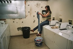Michelle Laundry 2 (neohypofilms) Tags: blue light brown color slr film girl 35mm cool shoes basket pants legs candid 28mm wideangle clothes jeans negative laundry slacks clogs ambient series casual machines mules washers folding dyers pentex