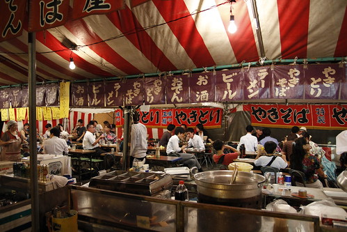 People eating at the food stalls during Mitama Matsuri