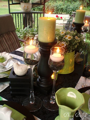 Pillar candles flank each side of the centerpiece Two glass stemmed pieces