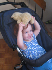 Speck in stroller, grinning, with teddy bear lying on her head
