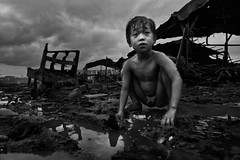 Typhoon Esther in Ulingan (charcoal) , Tondo, Manila - Abandoned chair and forgotten childhood (Mio Cade) Tags: boy portrait cloud baby rain childhood kid chair asia mood play mud flood philippines social manila esther typhoon reportage tondo
