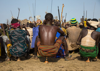 Tribe warriors during the proud ox ceremony in the Dassanech tribe waiting to share the cow meat, Turkana County, Omorate, Ethiopia