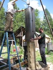 lowering the insulation tube (fishermansdaughter) Tags: yurt cob floorheater heatingwithwood rocketmassheater unconventionalwoodstove cleanburningwoodstove selfbuiltstove