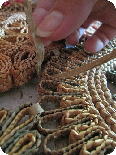 slipping raffia through spaces in straw trivet