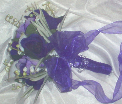 *kirsty 969 po* a brides bouquet of calla lilies/ purple enemones/purple roses/lily of the valley/spider leaves/diamante pins/purple gems,and finished with a pretty purple bow by you.