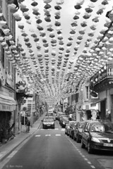 Street in Montignac - 2 (Ben Heine) Tags: street camera bridge light party wallpaper sky blackandwhite copyright france art cars tourism clouds composition print poster lens landscape photography lights vanishingpoint focus holidays shadows dof village cloudy pov earth lumière decorative space flag horizon country transport decoration perspective arts creative atmosphere tunnel dordogne celebration ciel montignac terre pont périgord conceptual rue reproduction connection contrejour ombres paperflower cs4 makadam acquitaine benheine flickrunited samsungnx10 infotheartisterycom