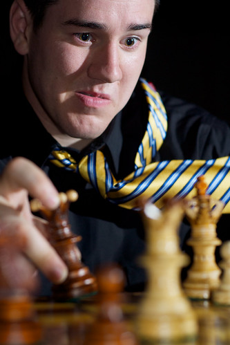 man playing chess with a very focused look in his eyes