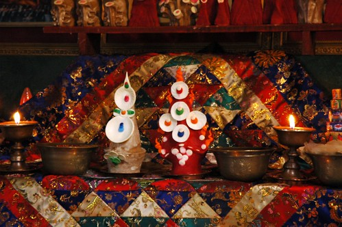 Torma offerings, candles, ritual cloth, shrine set up at Sakya Lamdre, Tharlam Monastery of Tibetan Buddhism, Boudha, Kathmandu, Nepal by Wonderlane