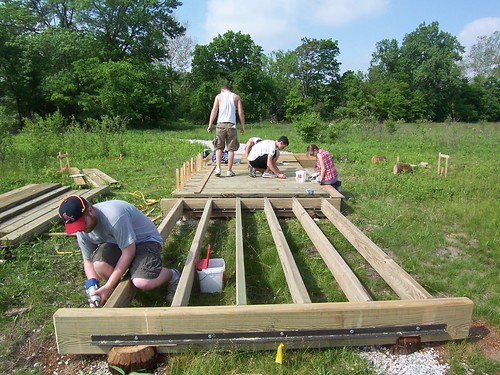 Members of the John M. Craddock Wetland Nature Preserve Team construct a walkway through a wetland in Muncie, Ind.