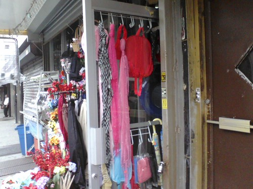 Dollar Store Door in Bay Ridge, Brooklyn.  Shows a series of scarves hanging; the one on the far left is a kuffiyeh.