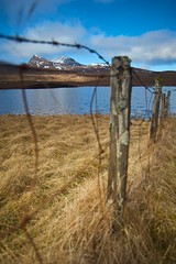 BarbWireMr (Leathanach) Tags: wood blue mountain water grass clouds fence scotland highlands nikon hill barbedwire loch assynt d700 landscapesshotinportraitformat clanflickr