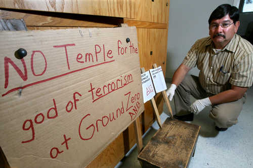 a sad-looking man crouches next to a crudely made cardboard sign that reads No temple for the God of terrorism at Ground Zero