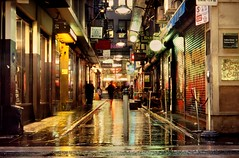 wanker lane, in the rain (mugley) Tags: street city longexposure people urban signs film wet rain bar night corner walking graffiti vanishingpoint fuji minolta pavement steps australia melbourne slide victoria scan explore sidewalk motionblur chrome lane transparency pedestrians epson pointandshoot cbd konica positive lamps storefronts footpath frontpage e6 bollard cafes urbanlandscape sensia centreplace sensia100 v700 rollerdoors ltcollinsst fujisensiaii100ra freedomzoom160 rivazoom160 minoltafreedomzoom160 wankerlane