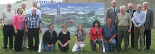USDA and local officials in front of a rendering of the newly designed learning facility.