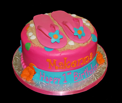 Bright colored luau themed first birthday cake with flip flops
