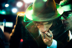 A Word in Your Ear (TGKW) Tags: light portrait people man green hat fashion night glasses whispering bokeh glasgow cigarette candid smoke smoking ring jewellery ear flare conversation nightlife omar spectacles speaking rayban rollie yoann 5540