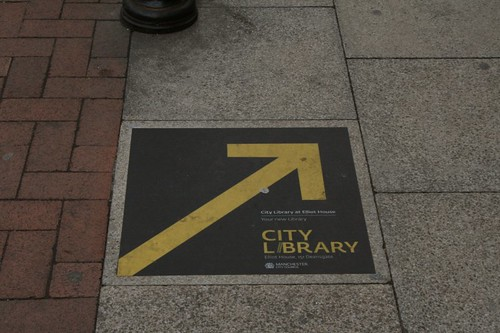 sign painted on pavement: City Library this way and big arrow pointing the way
