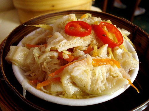 A small white dish of sliced leaf tripe (book tripe) tossed with shreds of carrot and root ginger, with two slices of fresh red chilli perched on top.  The dish sits inside a bamboo steamer basket.