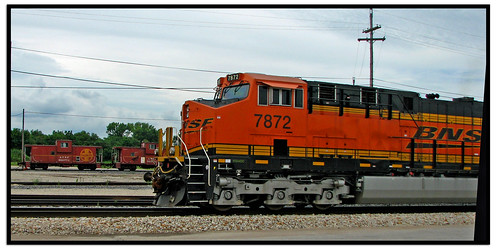 A train yard, with an orange locomotive in the foreground and two red cabooses in the background on another track.