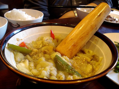 A white ceramic mortar with ridged, sloping sides and a brown border around the top.  The bowl is half-filled with a puree of steamed peeled aubergine, in which rests a smooth wooden pestle.  A few large slices of grilled green pepper are also visible.