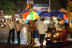 Caught in the Rain (pangalactic gargleblaster and the heart of gold) Tags: food rain traffic cart shelter umbrellas panning signal trade selling streetfood pushcart takenfromamovingbus