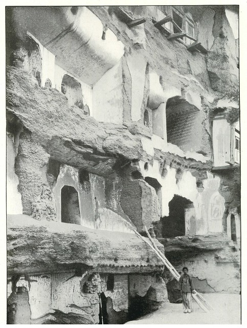 Rows of cave shrines, some showing decayed porches, near cave Ch. IX, Ch'ien-Fo-Tung, Tun-Huang.