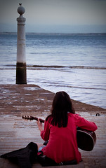 Playing for the sunset (campra) Tags: portugal water river meditate dusk lisbon solitary tejo pracadocomercio quai