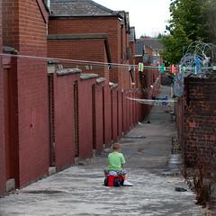 In the Alley (metroblossom) Tags: ireland playing alley catholic child unitedkingdom belfast barbedwire northernireland walls clotheslines bigwheel residential img3587 twelfth ardoyne thetwelfth