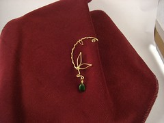 Ear cuff with thinner wire wrapped around it, making a vining look.