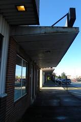 Dark Way to Go (haven't the slightest) Tags: trip summer vacation newfoundland dark pavement sidewalk storefronts shelter townsquare overhang 2010 gander elizabethave