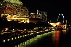 along the esplanade (Ron Layters) Tags: leica light reflection water skyline night buildings geotagged singapore asia downtown neon cityscape nocturnal skyscrapers harbour slide velvia esplanade transparency fujichrome singaporeriver r6 theatresonthebay singaporecity leicar6 ronlayters slidefilmthenscanned thesingaporeflyer   pelayangsingapura geo:lat=1289046212618143 geo:lon=1038544350355954