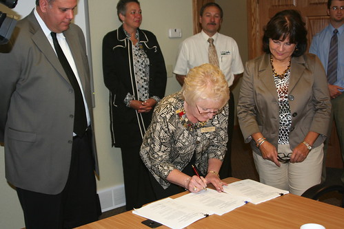 Joy McCracken – NeighborWorks Executive Director signs the Cooperative Packaging Agreement while State Director Elsie M. Meeks and Don Harris – Outreach Initiative Team Leader (USDA Rural Development National Office – Washington, DC) look on.