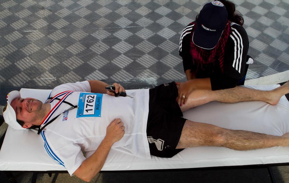 Roland Wenninger recibe masajes musculares de una asistente luego de su participación en la categoria 10km.  (Tetsu Espósito - Asunción, Paraguay)