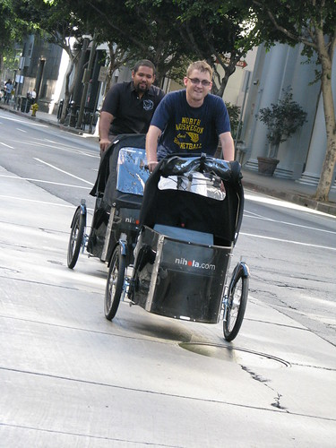 Eric Richardson, co-publisher of the Blogdowntown Weekly, and Steve Campos ride a pair of Nihola Family bikes through downtown LA.